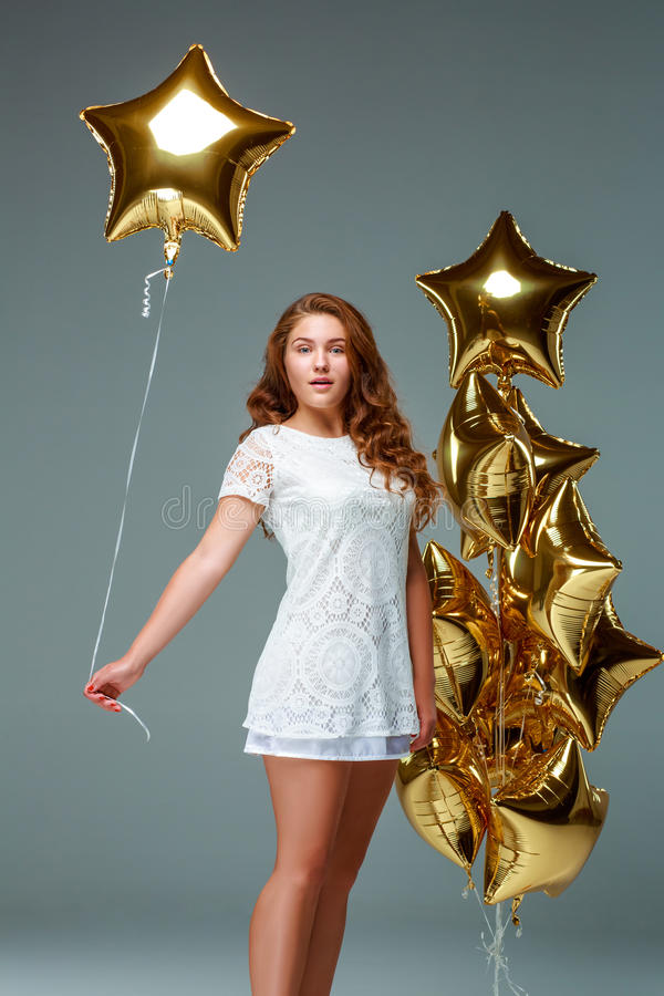 Portrait young attractive woman in white dress, holding bunch of. Portrait of a young attractive woman in a white dress, holding bunch of many gold balloons royalty free stock photography