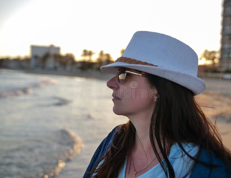 Portrait of a young attractive woman in a white hat looks at the sea royalty free stock photos