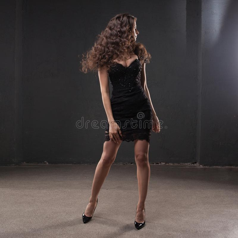 Portrait of a young attractive woman with gorgeous curly hair. young brunette in small black dress stock image