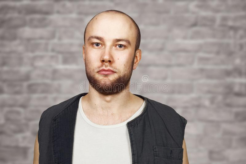 Portrait Young bald guy with beard with pocker face dressed in sleeveless shirt. Man on brick wall background stock image