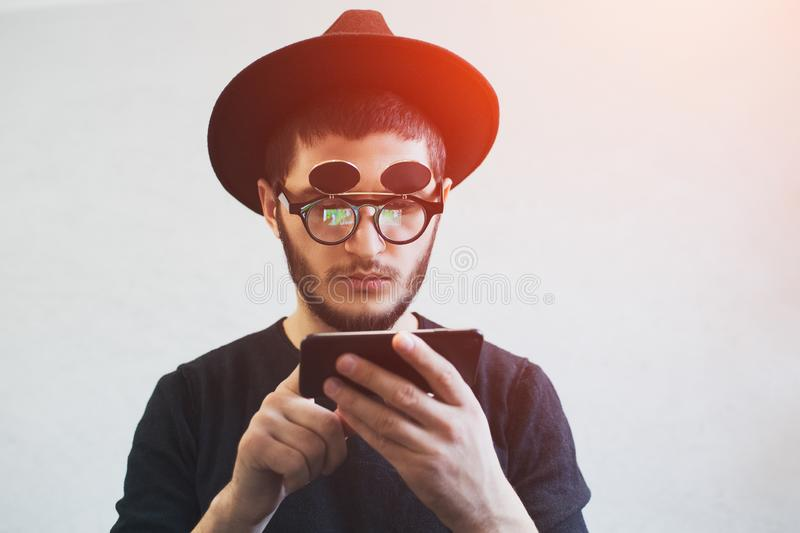 Portrait of young bearded guy using smartphone over white background. Wearing sunglasses and hat. Portrait of young bearded guy using smartphone over white stock photo