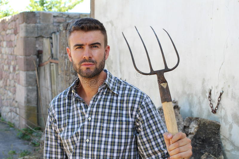 Portrait of young bearded handsome farmer in casual checkered shirt with old pitchfork on rustic background stock photo