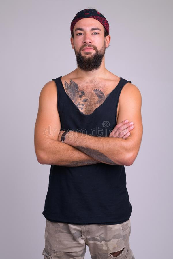 Portrait of young bearded handsome rebellious man with arms crossed stock photography