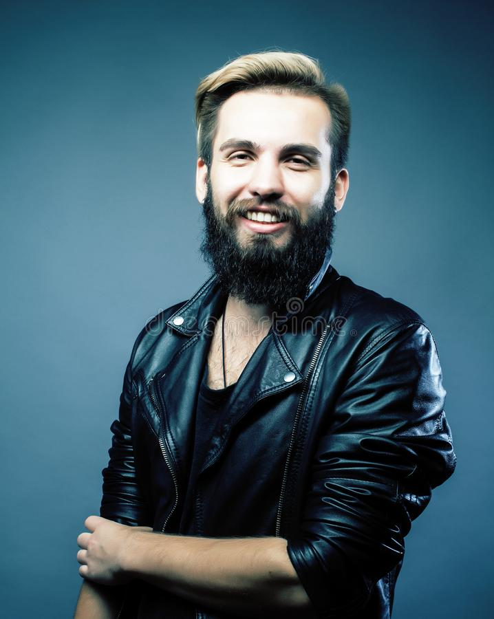 Portrait of young bearded hipster guy smiling on gray background royalty free stock images