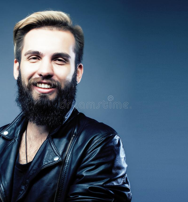 Portrait of young bearded hipster guy smiling on gray background stock image
