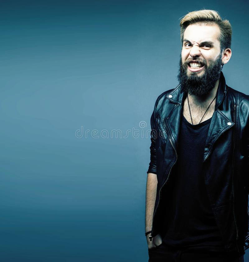 Portrait of young bearded hipster guy smiling on gray background royalty free stock image