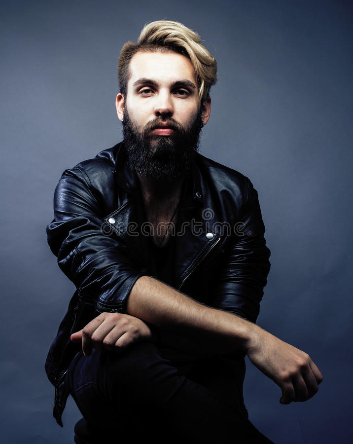 Portrait of young bearded hipster guy smiling on gray dark background close up, brutal modern man, lifestyle people royalty free stock photo