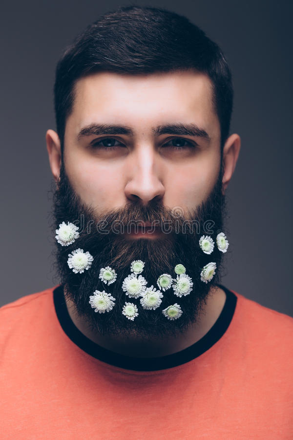 Portrait of young bearded hipster man with flowers in his beard royalty free stock photography