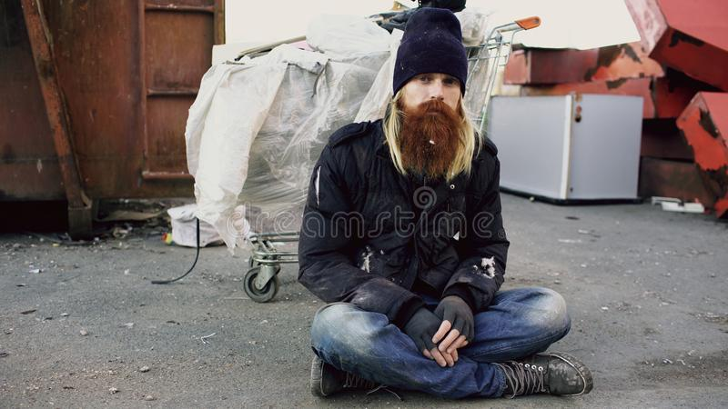 Portrait of young bearded homeless man sitting on a sidewalk near shopping cart ang garbage container during cold winter stock photography