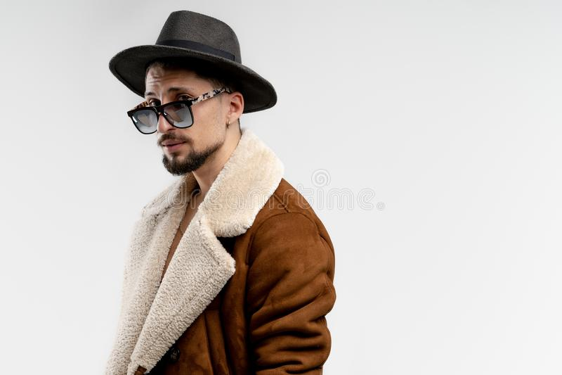 Portrait of young bearded man in black hat and brown coat in black sunglasses isolated over white background, copyspace stock photo