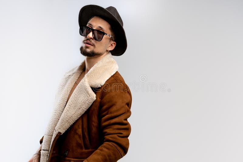 Portrait of young bearded man in black hat and brown coat in black sunglasses isolated over white background, copyspace royalty free stock image