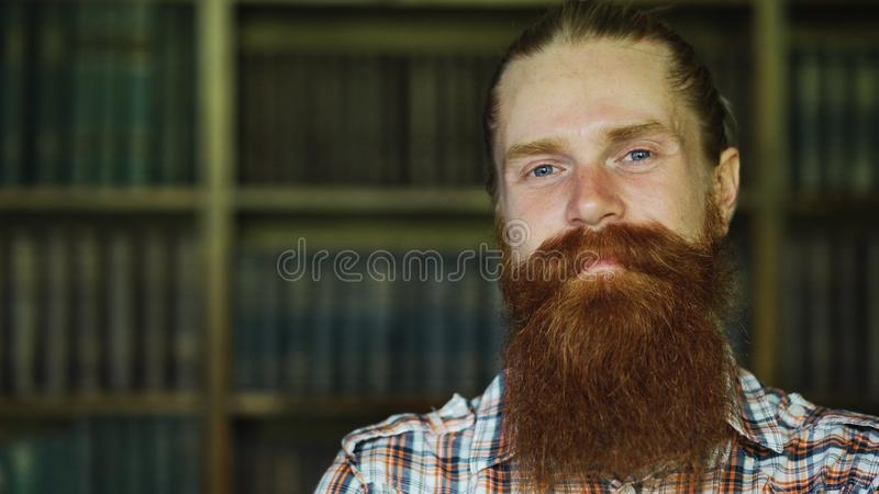 Closeup portrait of young bearded man smiling happy in library and looking into camera stock photo