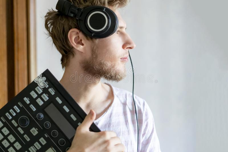 Portrait of young bearded man sound producer holding midi controller and headphones f royalty free stock photo