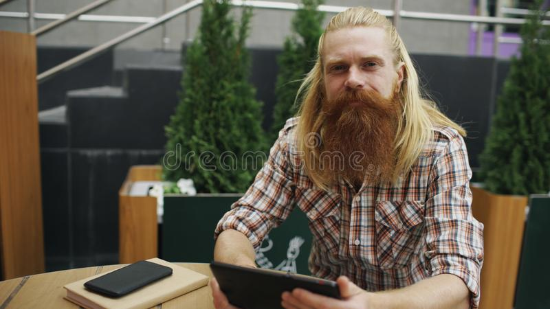 Portrait of young bearded man with tablet computer sitting in cafe outdoors smiling and having relax and resting of work stock photos