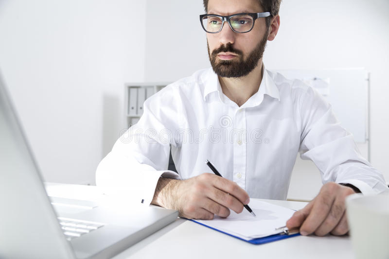 Portrait of a young bearded man taking notes stock photography