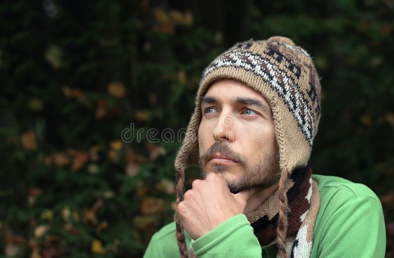 portrait of a young bearded man in warm hat on autumn forest background. wistful smile on his face. fall mood concept royalty free stock photos