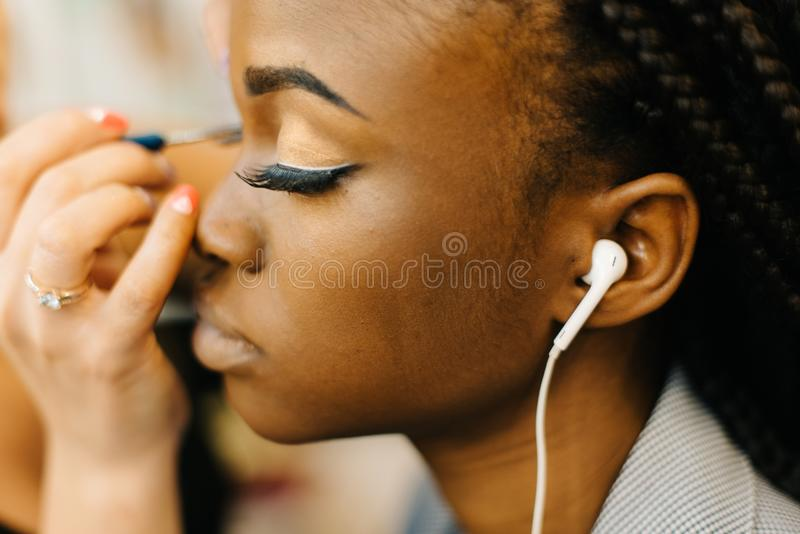 Portrait of the young beautiful african girl listening to music and receiving the make-up from professional make-up stock images