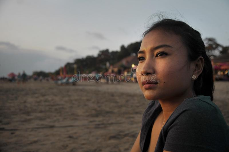 Beautiful Asian lonely woman looking to infinity lost in her thoughts sad and thoughtful sitting on sand beach. Portrait of young beautiful Asian lonely woman stock photos