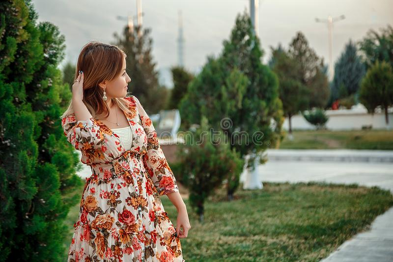 Portrait of a young beautiful Asian skinny slender woman in a floral print dress standing outside during sunset royalty free stock photography