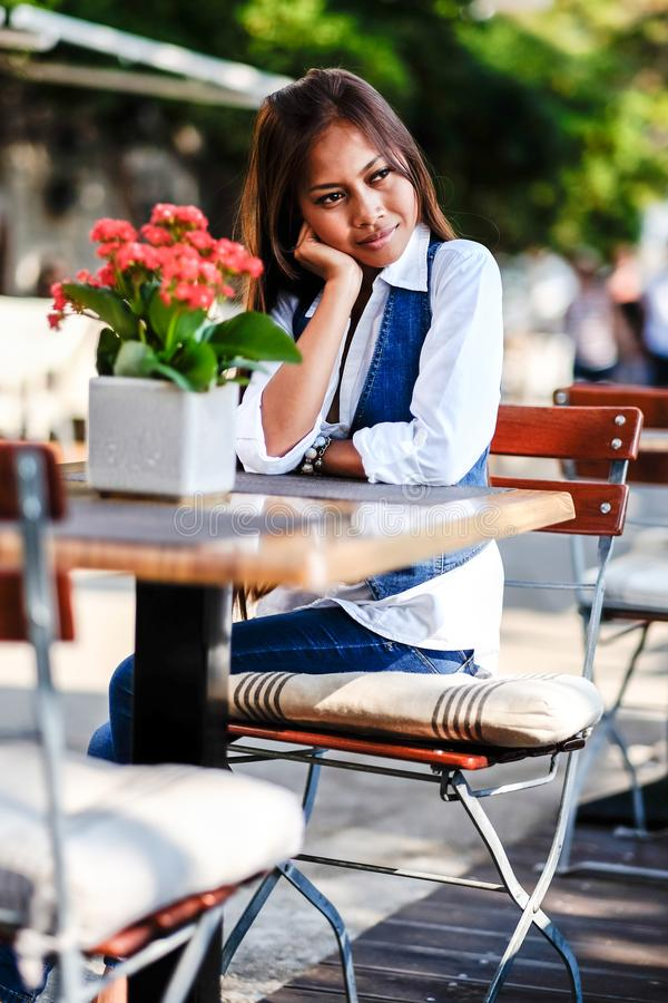 Portrait of young beautiful Asian woman alone at the cafe waiting and day dreaming.  stock image