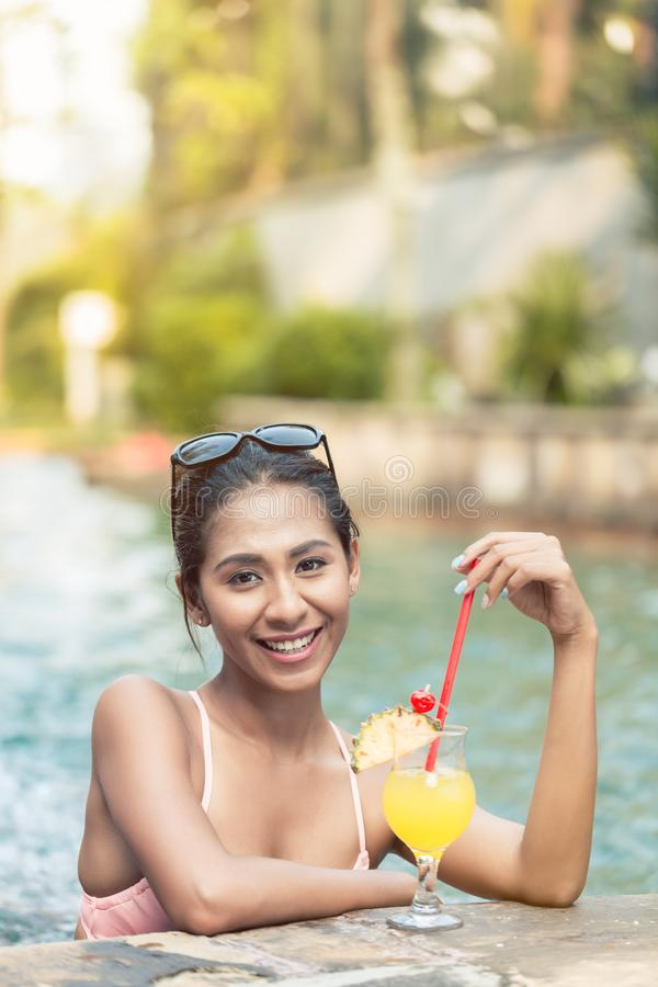 Portrait of a beautiful Asian woman drinking a pineapple cocktail in the pool stock photos