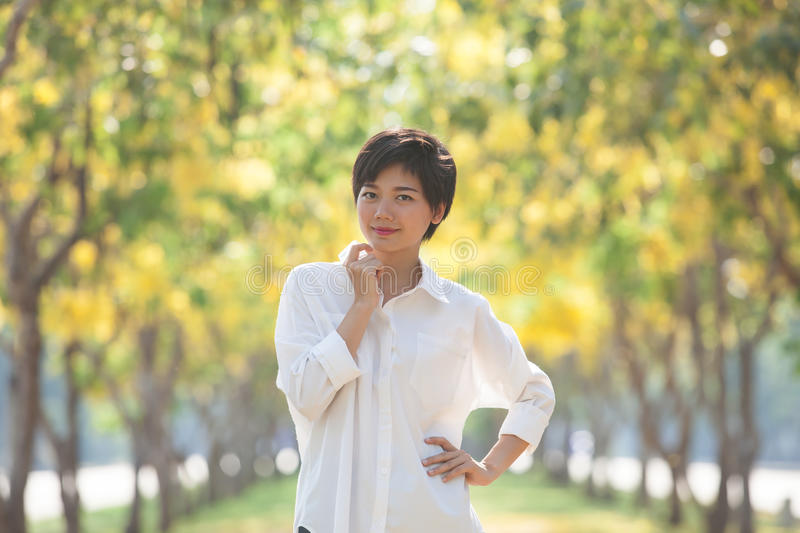 portrait of young beautiful asian woman with white shirt standing and smiling face in blur yellow flowers blooming background use royalty free stock photography