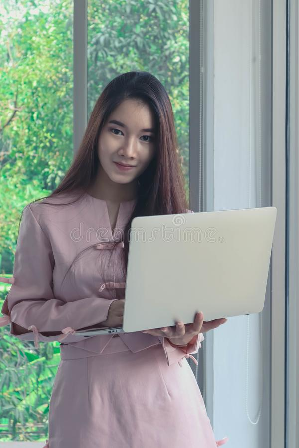 Portrait of young beautiful and attractive Asian business woman with smiling in pink dress hold labtop in modern officeas a royalty free stock images