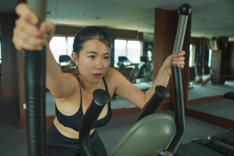 Portrait of young beautiful and attractive Asian Chinese woman training at hotel gym or fitness club working hard in cardio. Workout portrait of young beautiful stock images