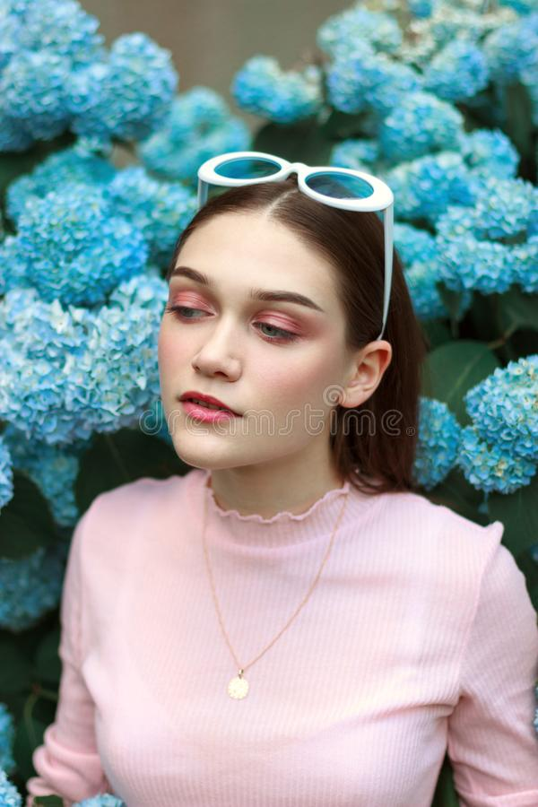 Portrait of young beautiful attractive woman with tender makeup in pink t-shirt, with white sunglasses on her head stock photo