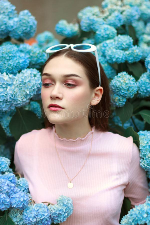 Portrait of young beautiful attractive woman with tender makeup in pink t-shirt, with white sunglasses on her head royalty free stock photography