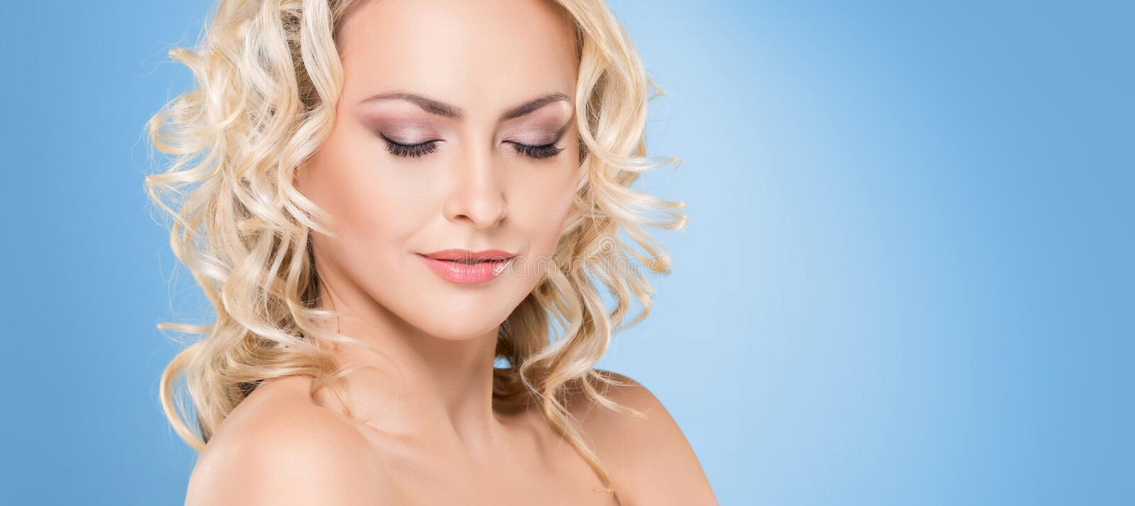 Portrait of young and beautiful blond girl with curly hair. Face lifting and beauty concept. stock image