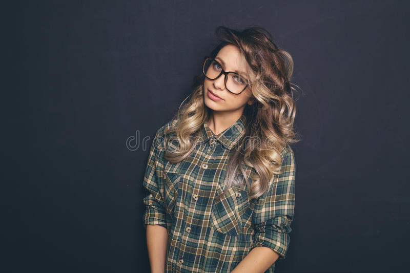 Portrait of a young beautiful blond-haired wearing trendy glasses and casual clothes and posing over black background stock photos