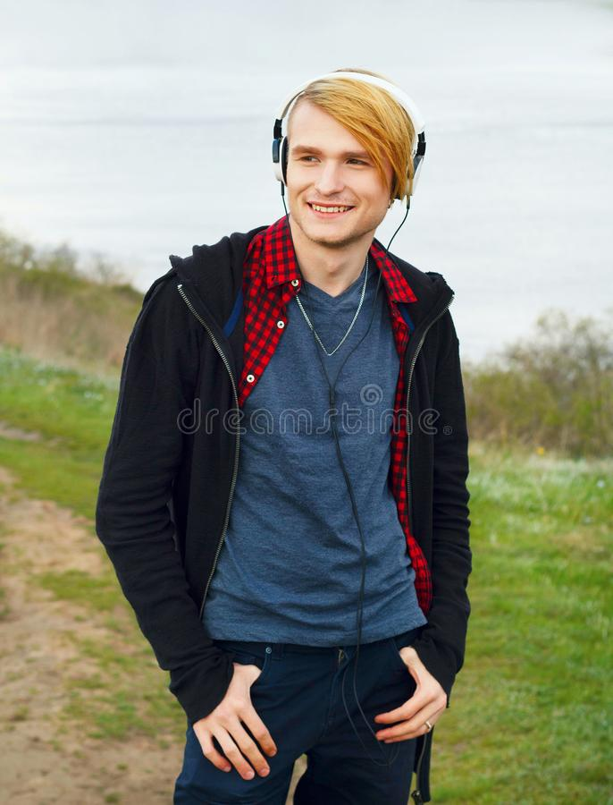 Portrait of young beautiful blond hipster man with headphones st royalty free stock images
