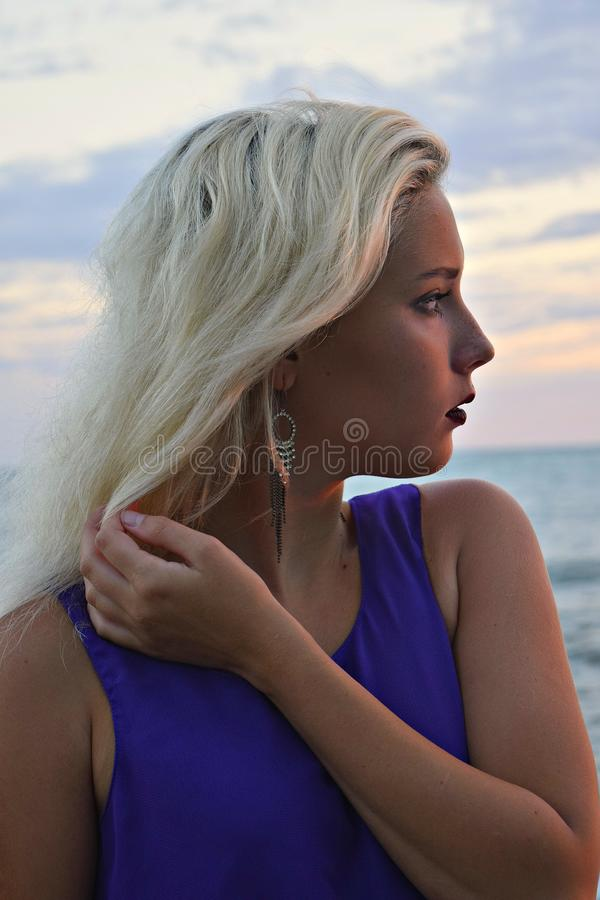 Portrait of young beautiful blonde girl on background of sky royalty free stock image