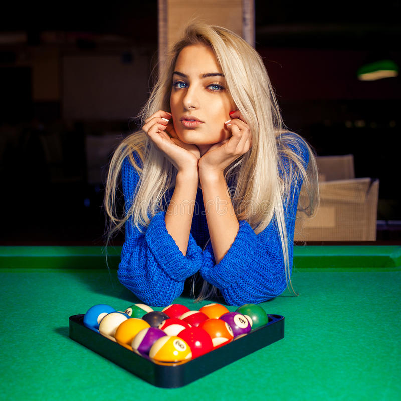 Portrait of young beautiful blonde girl with pyramid of pool balls stock images