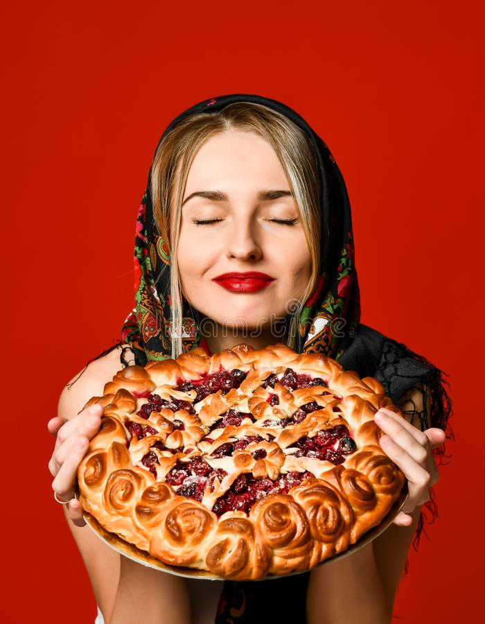 Portrait of a young beautiful blonde in headscarf holding a delicious homemade berry pie. stock images