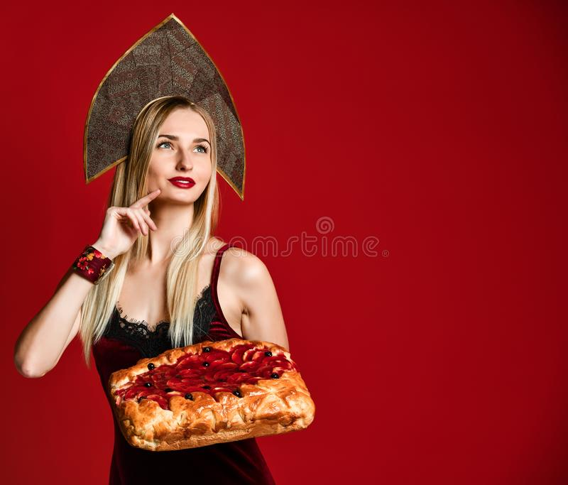 Portrait of a young beautiful blonde holding a delicious homemade cherry pie. stock images