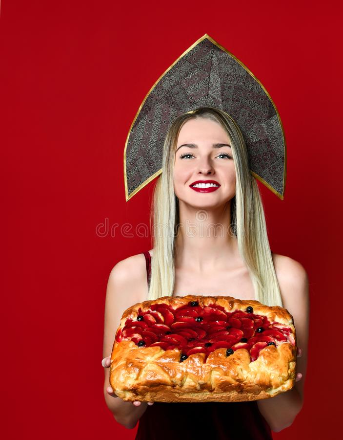 Portrait of a young beautiful blonde in kokoshnik holding a delicious homemade cherry pie. royalty free stock photo