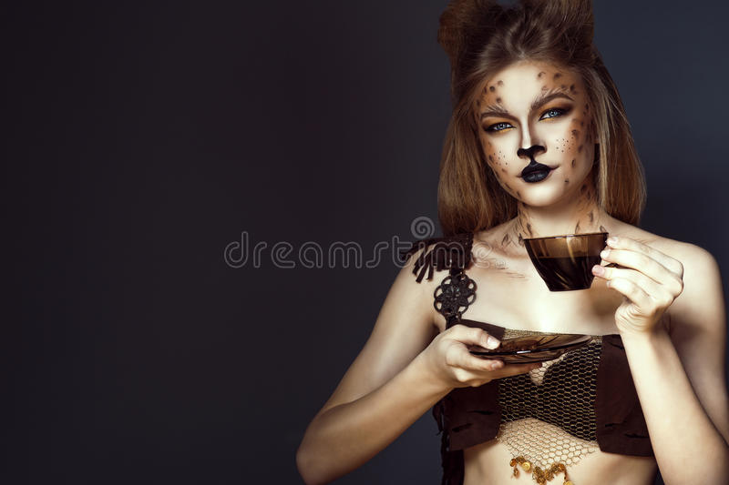 Portrait of young beautiful blue-eyed model with artistic leopard make-up drinking coffee royalty free stock photography