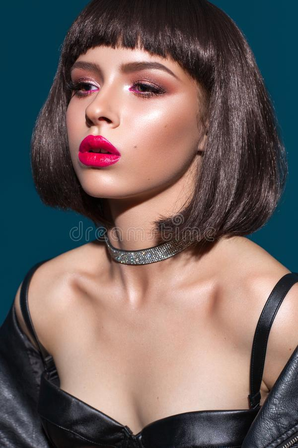 Portrait of young beautiful brunette model with colorful professional make up, bob hairstyle, red lipstick and eyeliner. Portrait of young beautiful brunette stock image