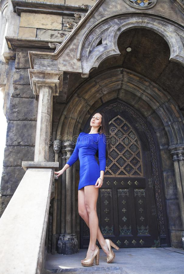 Portrait young beautiful brunette woman in blue dress posing against the backdrop of an old castle in the Gothic style. Full-length portrait young beautiful stock photos