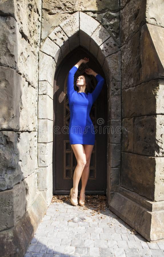Portrait young beautiful brunette woman in blue dress posing against the backdrop of an old castle in the Gothic style. Full-length portrait young beautiful stock photo