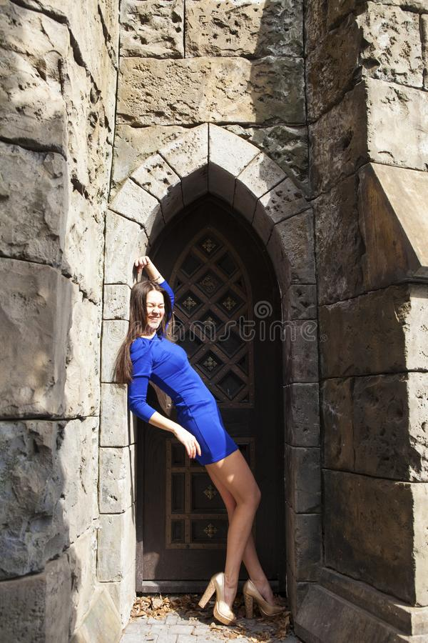 Portrait young beautiful brunette woman in blue dress posing against the backdrop of an old castle in the Gothic style. Full-length portrait young beautiful royalty free stock photos