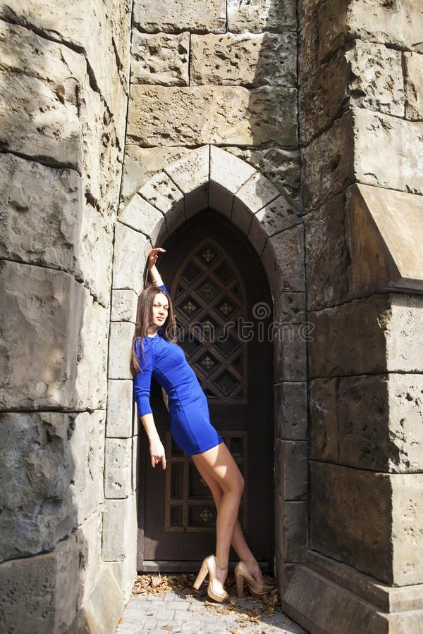 Portrait young beautiful brunette woman in blue dress posing against the backdrop of an old castle in the Gothic style. Full-length portrait young beautiful stock photography