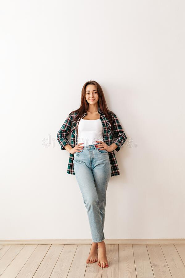 Portrait of a young beautiful brunette woman in casual clothes posing on a white background. Copy space. Vertical orientation.  stock photography