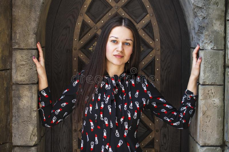 Portrait young beautiful brunette woman in dress posing against the backdrop of an old castle in the Gothic style. Close up portrait young beautiful brunette stock photography