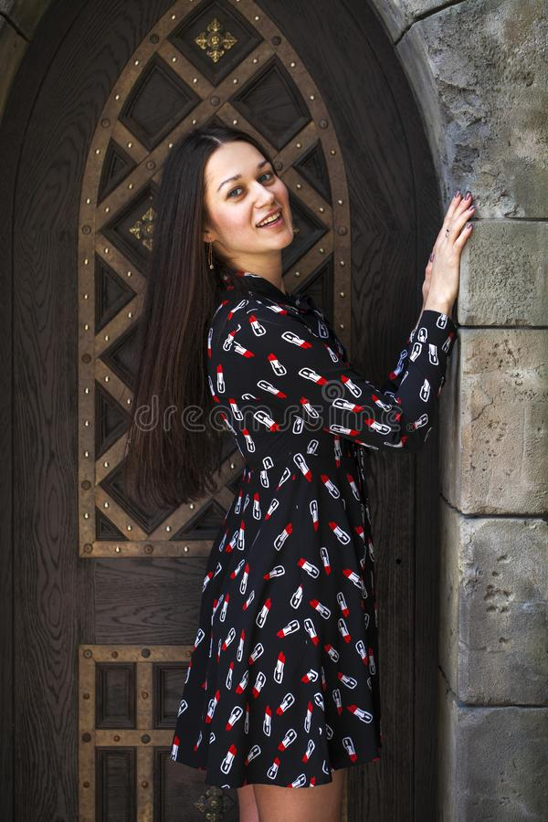 Portrait young beautiful brunette woman in dress posing against the backdrop of an old castle in the Gothic style. Close up portrait young beautiful brunette royalty free stock photo