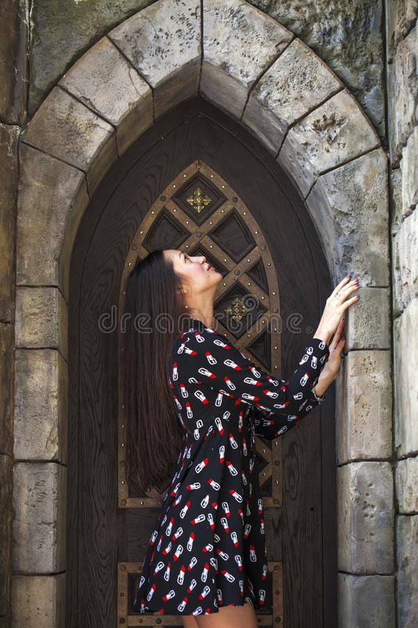 Portrait young beautiful brunette woman in dress posing against the backdrop of an old castle in the Gothic style. Close up portrait young beautiful brunette stock images
