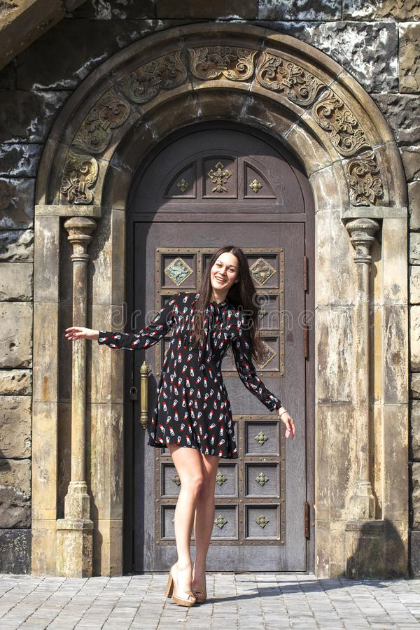 Portrait young beautiful brunette woman in dress posing against the backdrop of an old castle in the Gothic style. Full body portrait young beautiful brunette royalty free stock photos
