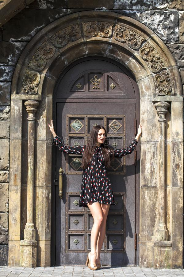 Portrait young beautiful brunette woman in dress posing against the backdrop of an old castle in the Gothic style. Full body portrait young beautiful brunette stock images